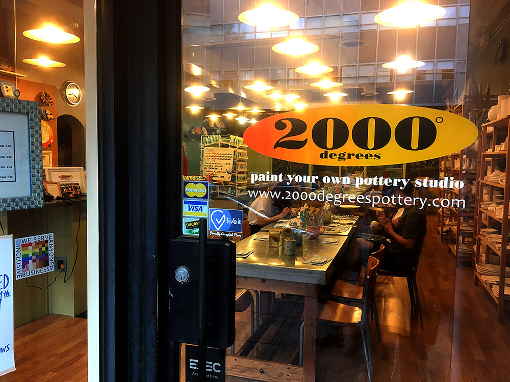 The 100% Sign is seen in the window adjacent to the entrance to 2000 degrees pottery studio. People can be seen inside decotrating pottery