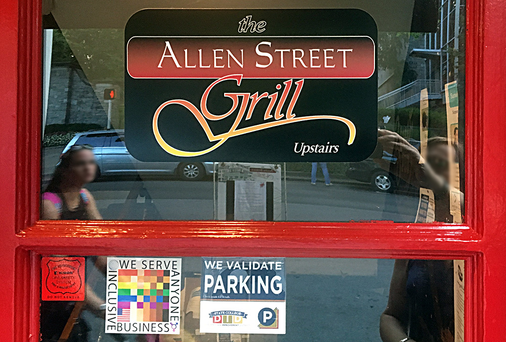 The 100% Sign is seen in the window of a red door below the logo for the Allen Street Grill restaurant in State College, PA