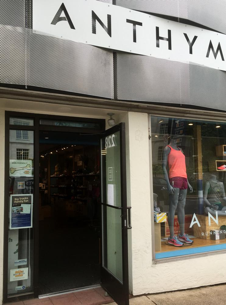 The 100% sign is seen in the entryway of the Anthym running store. Mannequins are also visible in the window.