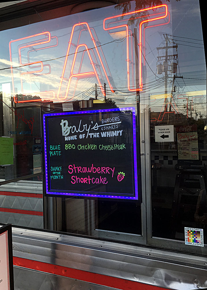 The 100% Sign is seen in a window of Baby's diner beside a chalk board and a big neon sign that says eat.