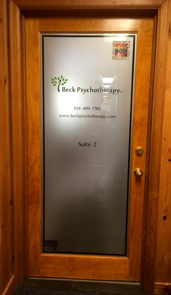 An office suite door is shown with the bumper sticker version of the 100% sign on display