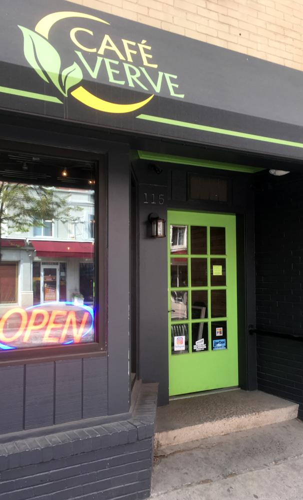 The 100% sign is seen on the doorway to cafe verve
