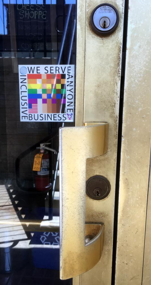 A 100% sticker is seen in close up beside the hand of the shop entry door