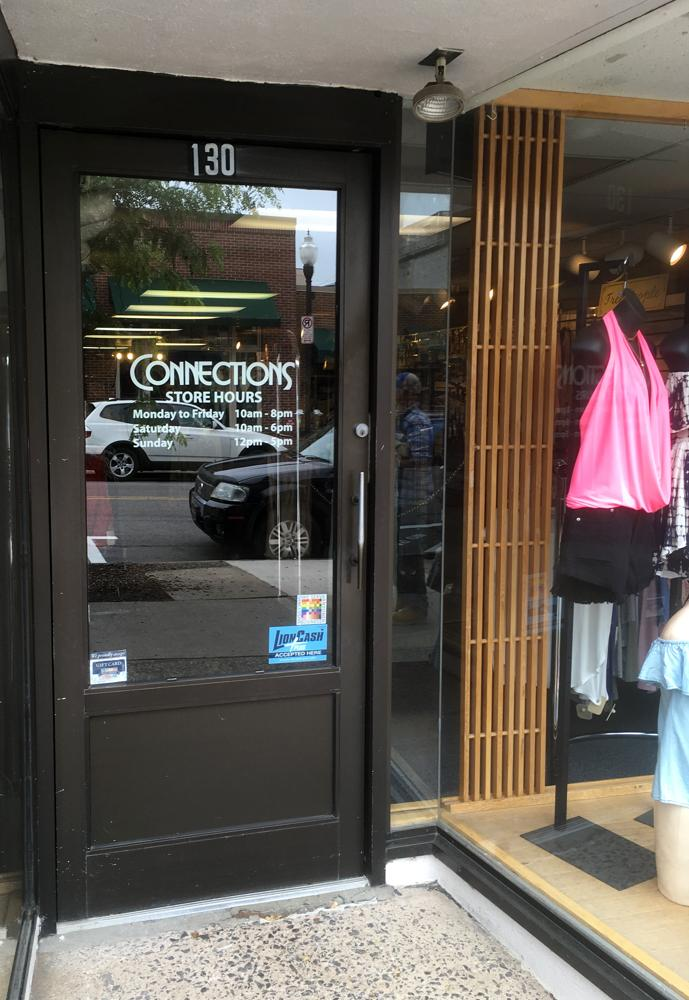 The 100% sign is seen in the entry door to Connections clothing boutique. A mannequin is also visible