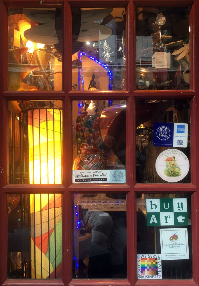 The 100% sign is seen in a multipane window of the duoglas albert galler along with several object d'art