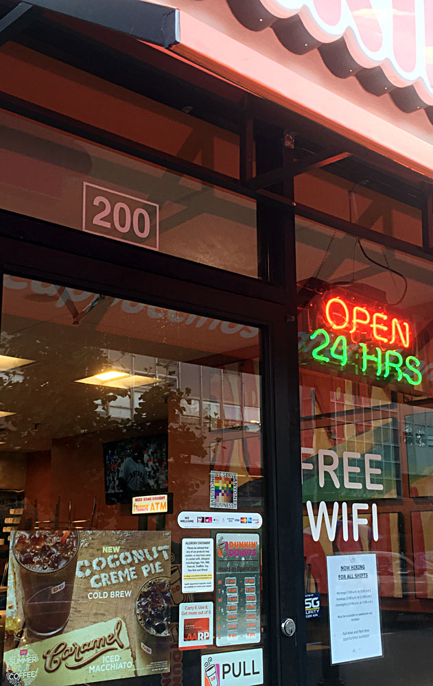 The 100% sign is seen in the doorway of Dunkin Donuts beside two signs that say open 24 hours and free wifi