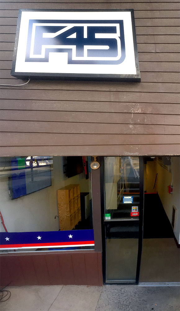 The 100% Sign is seen on a lower level entry door to F45 trainging. Above a is a large F45 logo on clapboard siding