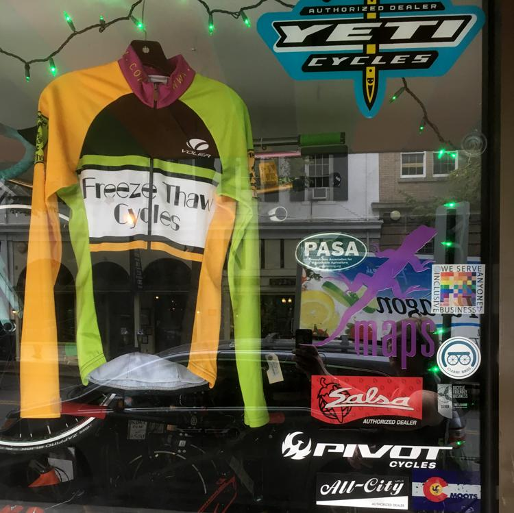 The 100% sign is seen in the Freeze Thaw Cycles shop window beside a cycling garment with the name of the store on it