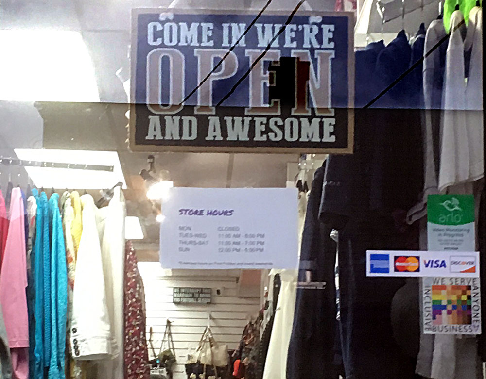 "The 100% sign is seen on the door to a store called Funky Trunk with a prominent sign that declares ""come in we're open and awesome"""