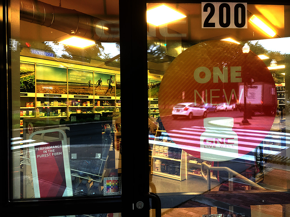 The 100% Sign is seen in the window of a GNC store with a bold number 200 on the door