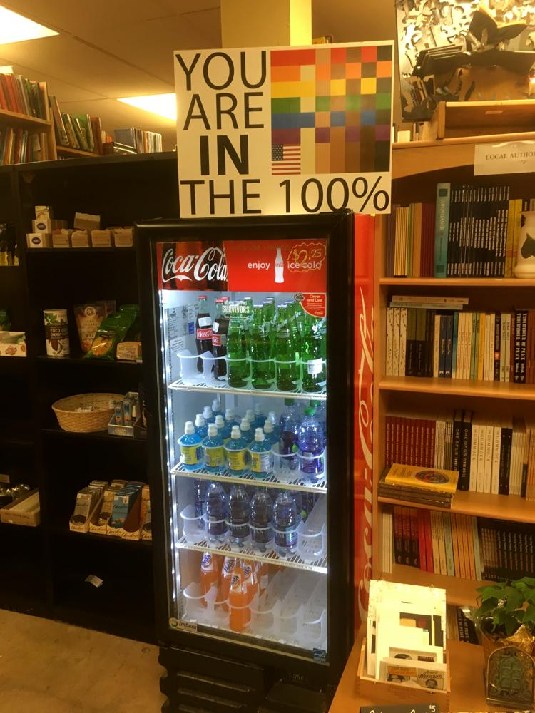 A 100% lawn sign sits atop a drinks cooler in Webster's bookstore