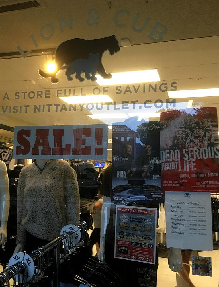 The 100% sign is seen in the window of the Lion and Cub, a store selling Penn State apparel