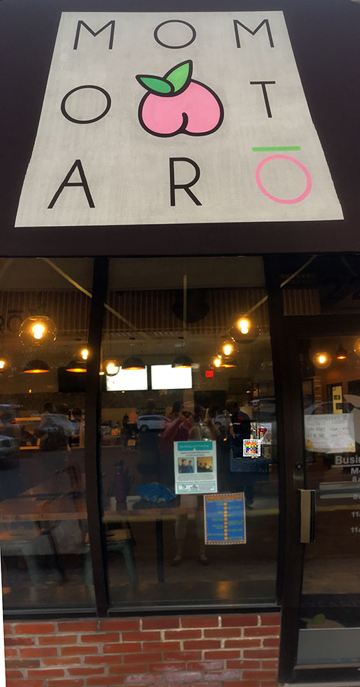 The 100% sign is seen in window of Momotaro a desert restaurant.