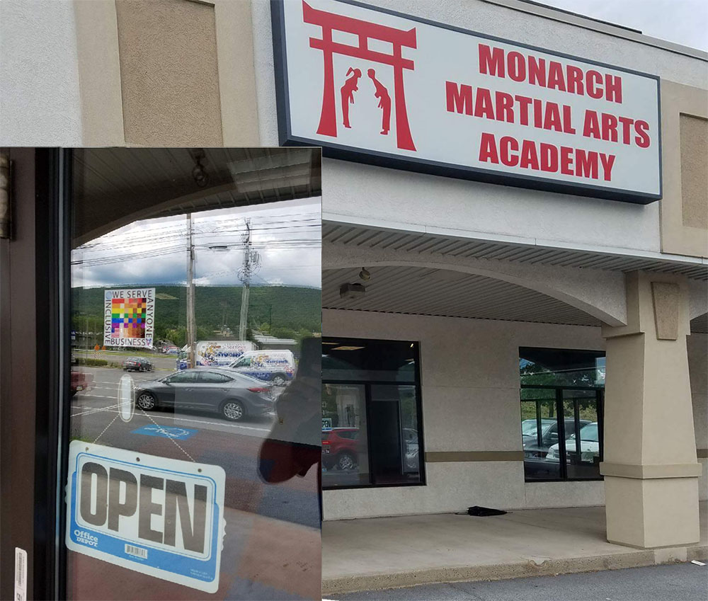 The 100% Sign is seen on th entry door to Monarch Martial Arts Academy in an inset that shows a wider view of the front of the building