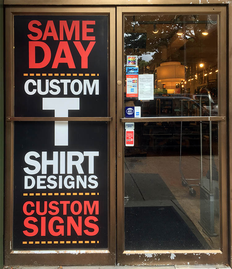 The 100% sign is seen on an entry door to the People's Nation boutique. One entire door is taken up by an advert for T-shirt printing