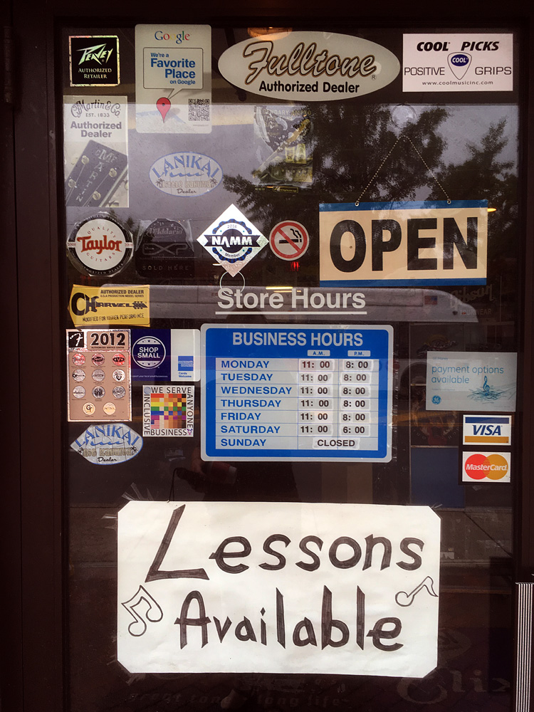 The 100% Sign is seen in the doorway to Rainbow Music guitar and instrument store a bold sign also announces lessons available