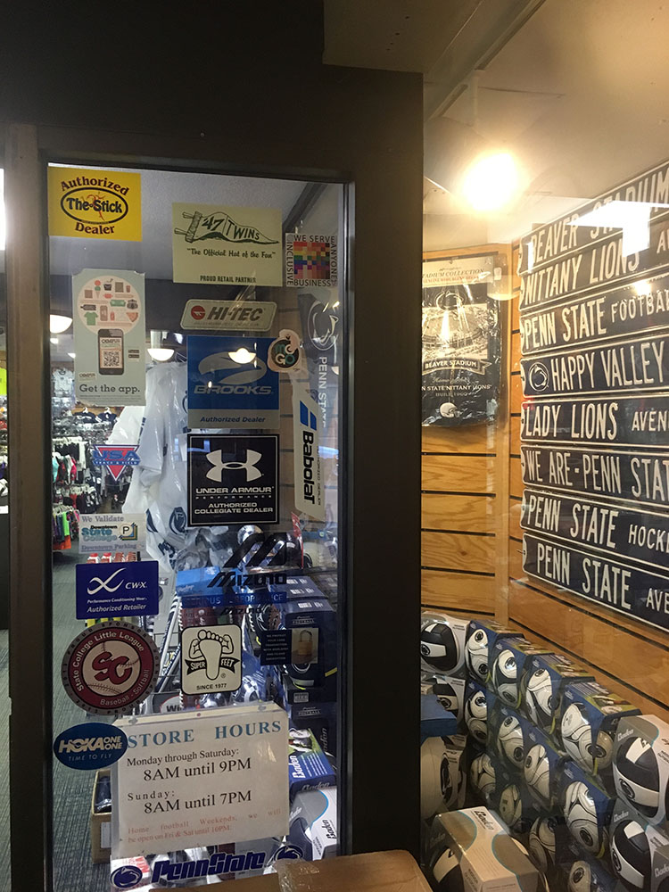 The 100% sign is seen at the top of an entry door to Rapid Transit Sports various sporting goods and Penn State Souveniers are also visible in the window