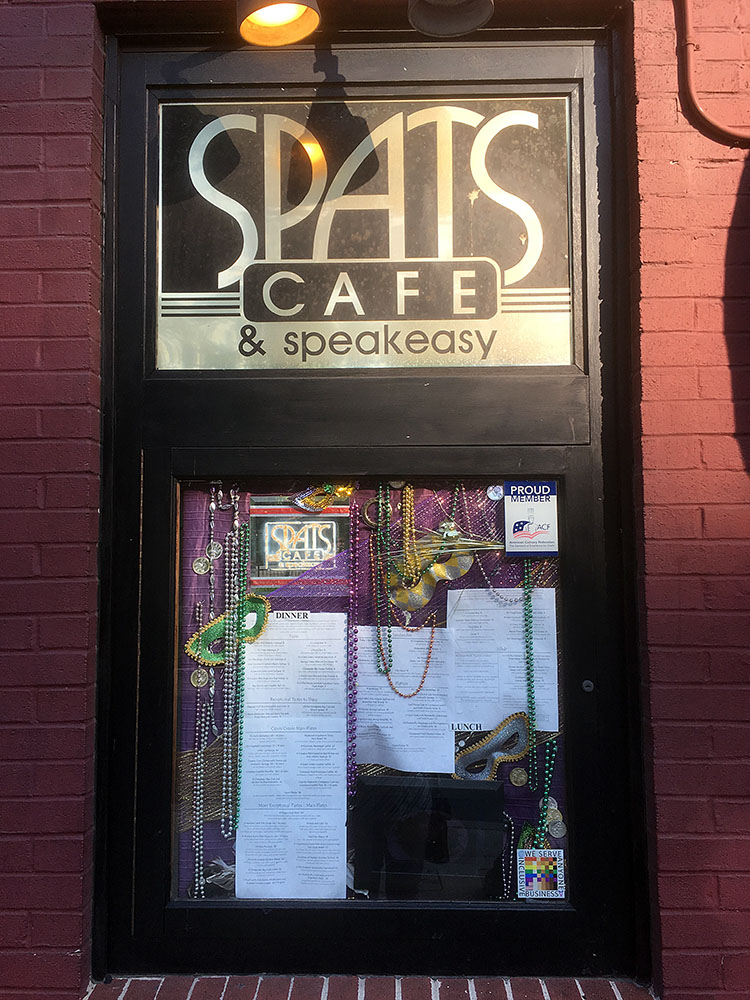 The 100% Sign is seen in the menu window of Spat's Cafe along with the menu and various mardi gras decorations