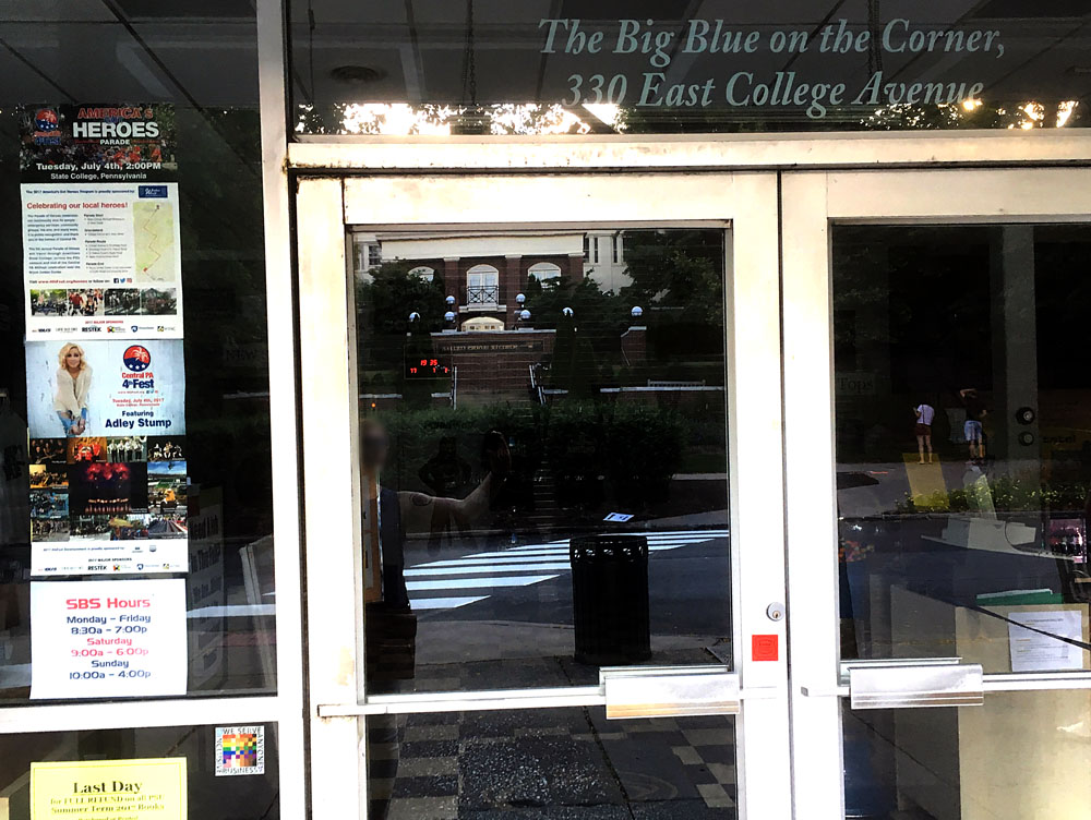 The 100% sign is seen in the doorway to the Student Bookstore. Above the door the store knickname the big blue on the corner is seen.