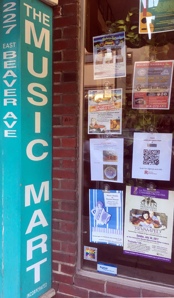 The 100% sign is seen low in the window of The Music Mart who's shop sign is a bold green column