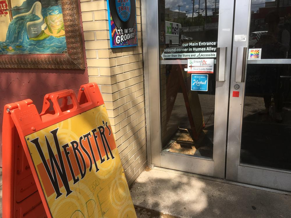 An entrance to Webster's Bookstore has a 100%Sign sticker on the entry door