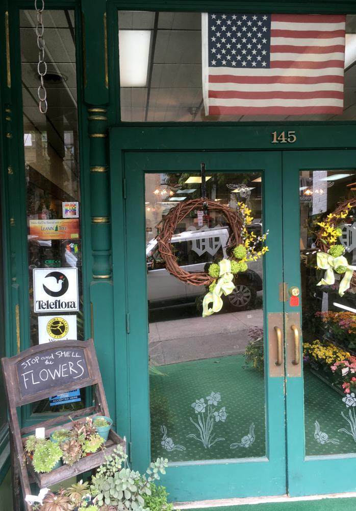 The 100% sticker is seen in the entrance to a florist above some flowers. There is also a large American flag above the doorway