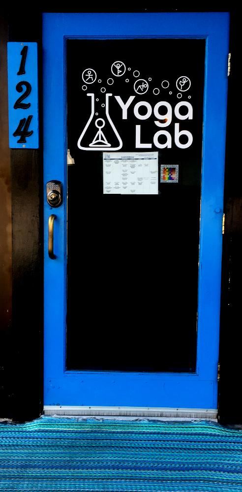 A 100% sticker is shown on the door to the Yoga lab studio