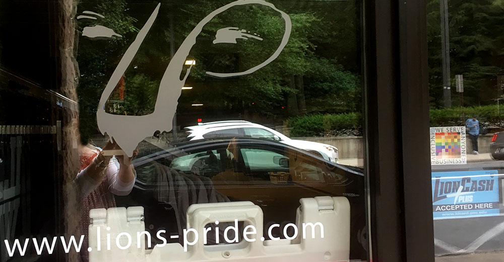 The 100% sign is seen in the front window of Lions Pride store with a schematized lion face painted on the window